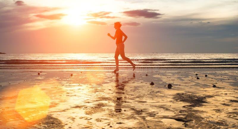 Siluetta di un pareggiatore della giovane donna al tramonto sulla spiaggia sport immagine stock libera da diritti
