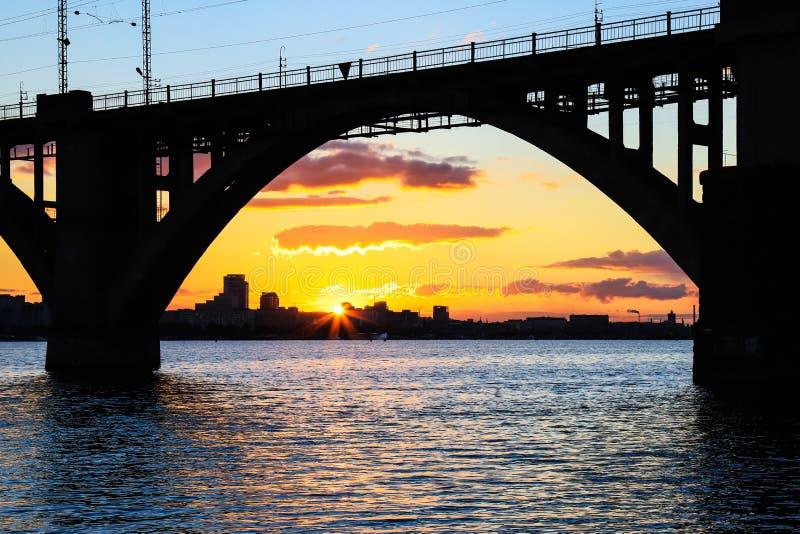Siluetta di un ponte ferroviario incurvato su un bello tramonto sul fiume di Dnieper nella città di Dnipropetrovsk immagine stock