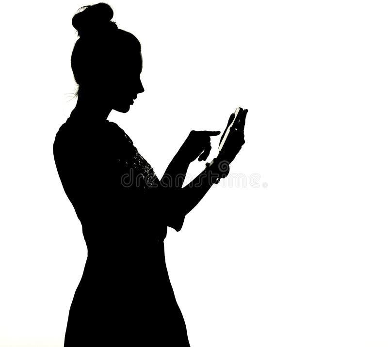 Siluetta di un uisng della donna lo smartphone immagini stock