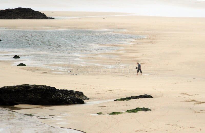 Siluetta di un uomo che cammina nella spiaggia immensa di Newquay, una destinazione popolare per i surfisti fotografie stock