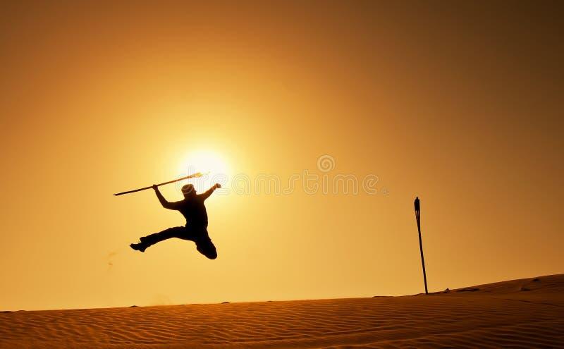 Siluetta di un uomo che salta con la freccia a disposizione fotografie stock