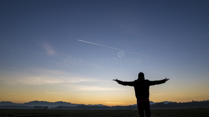Siluetta di un uomo che sta con il suo di nuovo alla macchina fotografica in un  immagine stock