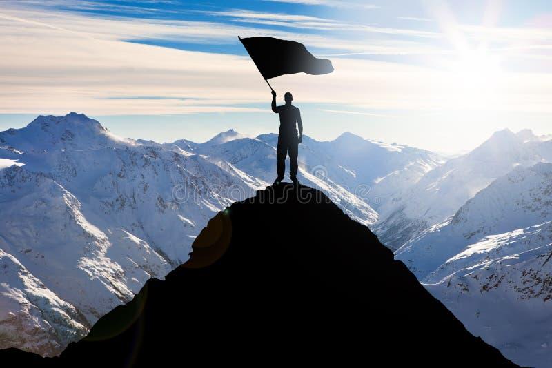 Siluetta di un uomo con la bandiera che sta sul picco di montagna fotografia stock libera da diritti