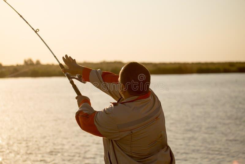 Siluetta di un uomo con una canna da pesca al tramonto fotografia stock libera da diritti