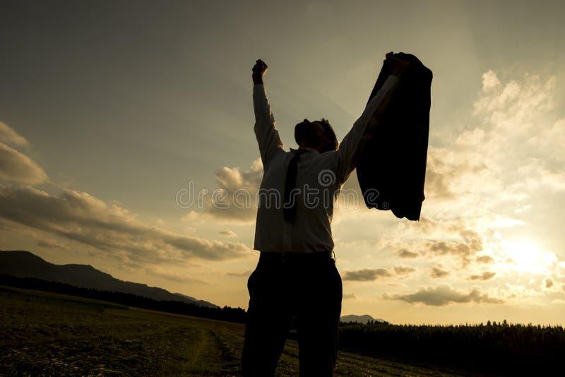 Siluetta di un uomo d'affari che alza il suo braccio fotografia stock
