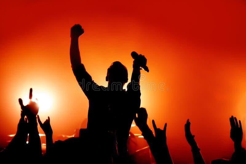 Siluetta di un vocalist che esegue ad un concerto rock fra i fan fotografie stock