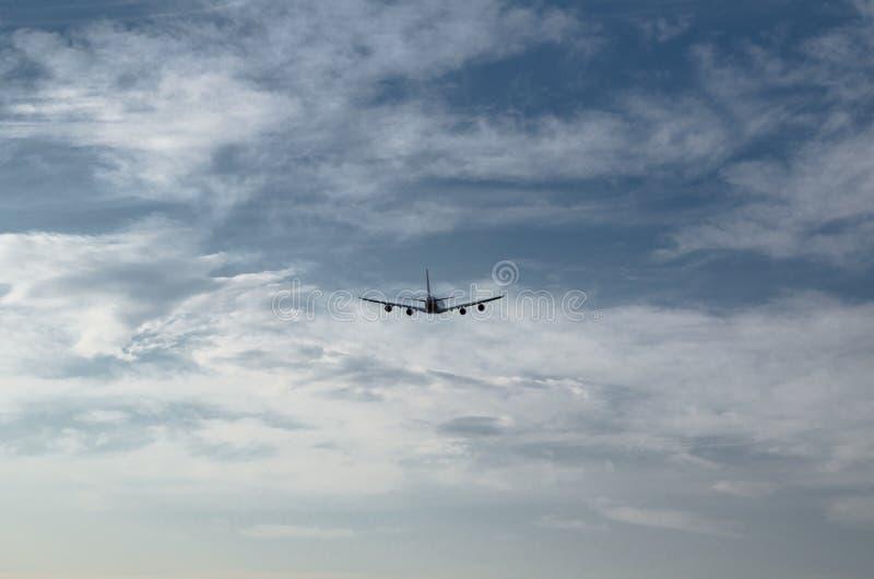 Siluetta di un volo dell'aeroplano isolata sul fondo di giorno del cielo nuvoloso fotografia stock