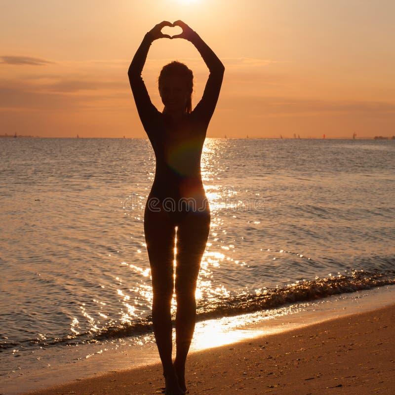 Siluetta di un'yoga di pratica della giovane donna alla spiaggia al tramonto fotografia stock