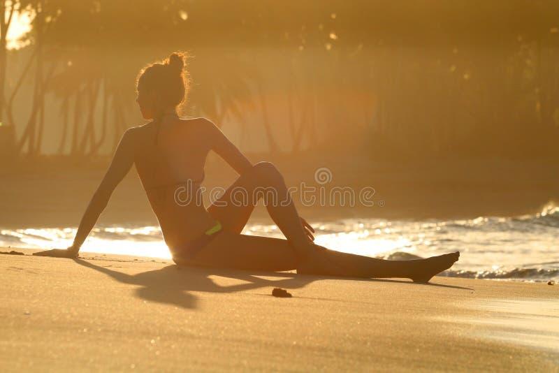 Siluetta di un'yoga di pratica della giovane donna sulla spiaggia al tramonto con le palme su un fondo immagine stock libera da diritti