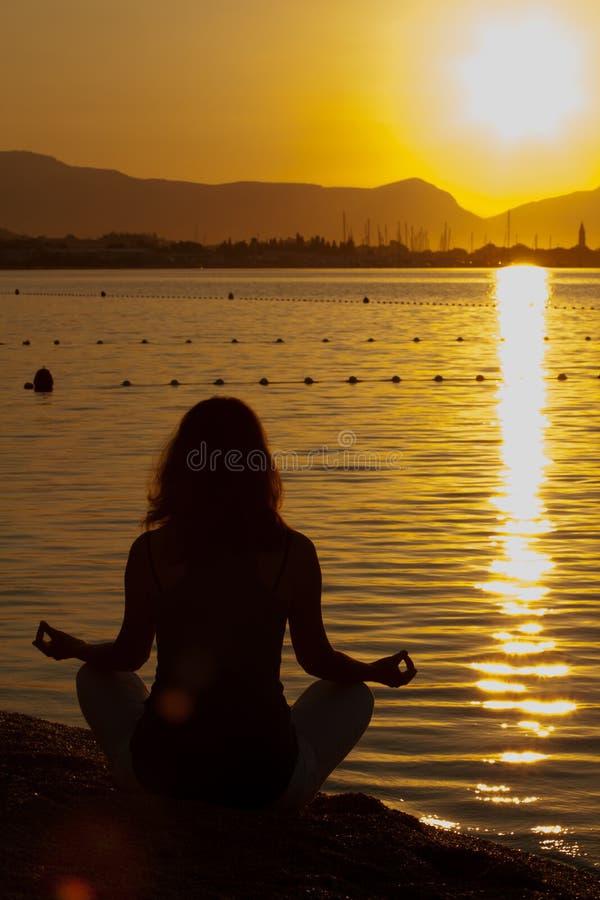 Siluetta di un'yoga excercising della bella donna fotografia stock libera da diritti