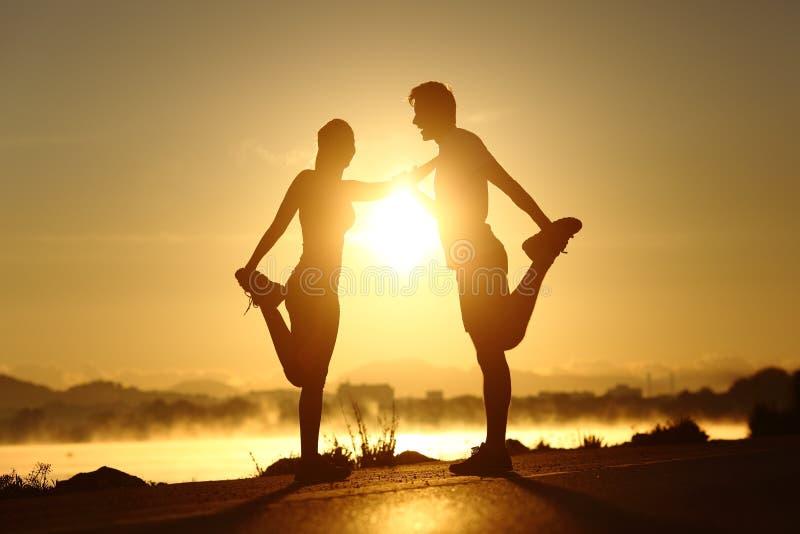 Siluetta di una coppia di forma fisica che allunga al tramonto fotografia stock