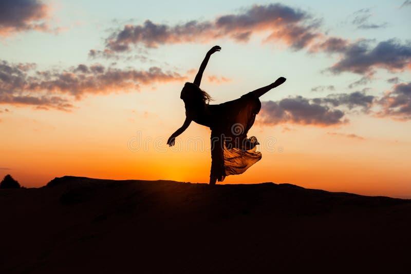 Siluetta di una donna al tramonto immagini stock