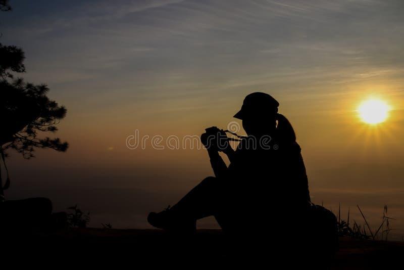 siluetta di una donna che tiene una macchina fotografica che prende le immagini fuori durante l'alba o il tramonto fotografia stock libera da diritti