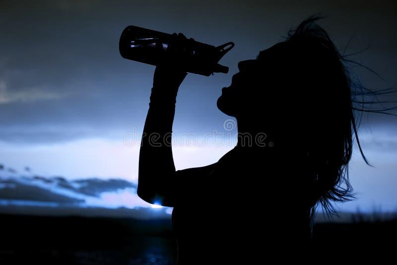Siluetta di una donna con una fine della bottiglia di acqua in su immagini stock libere da diritti