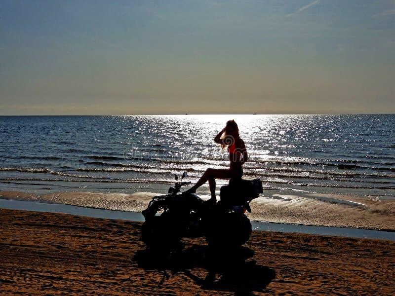 Siluetta di una donna dai capelli biondi lunghi seduta su una quad-bike, giorno soleggiato sulla spiaggia immagini stock libere da diritti