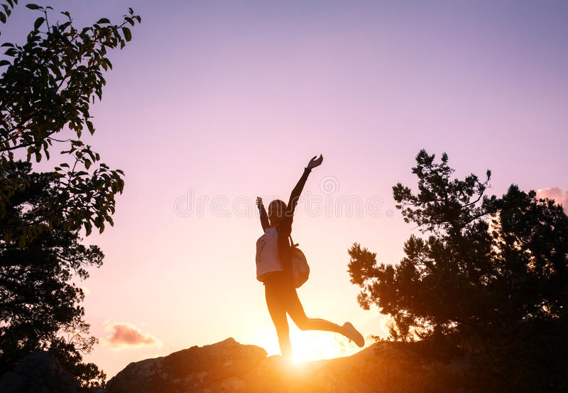 Siluetta di una giovane donna felice in montagne al tramonto fotografia stock