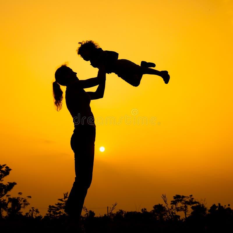 Siluetta di una madre e figlio che giocano all'aperto al tramonto fotografia stock libera da diritti