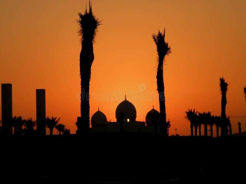 Siluetta di una moschea con il cielo arancio incorniciato dalle palme fotografia stock