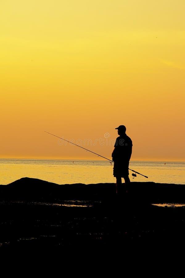 Siluetta di una pesca dell'uomo nel Mare del Nord contro l'incandescenza del cielo di sera dopo il tramonto fotografie stock libere da diritti