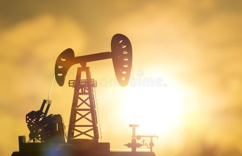 Siluetta di una pompa della trivellazione petrolifera fotografie stock libere da diritti