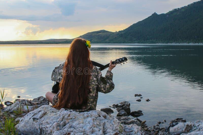 Siluetta di una ragazza al tramonto che gioca la chitarra dal fiume fotografia stock libera da diritti