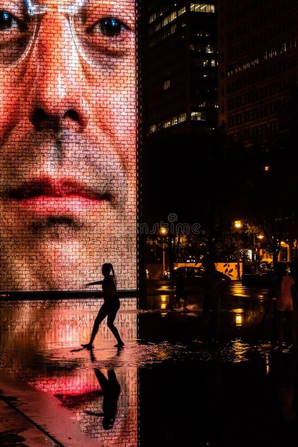 Siluetta di una ragazza che balla in uno stagno di acqua alla notte Sosta di millennio in Chicago immagine stock libera da diritti