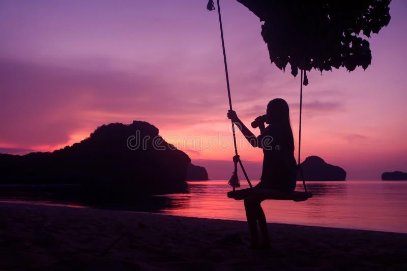 Siluetta di una ragazza che si siede su un'oscillazione o su una culla sulla spiaggia al tramonto fotografia stock libera da diritti