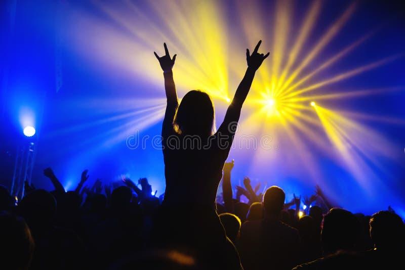 Siluetta di una ragazza del giovane fan ad un festival rock musicale immagine stock libera da diritti