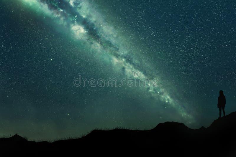 Siluetta di una ragazza su un paesaggio montagnoso alla notte contro un cielo blu in pieno delle stelle e di un latteo incredibil fotografie stock libere da diritti