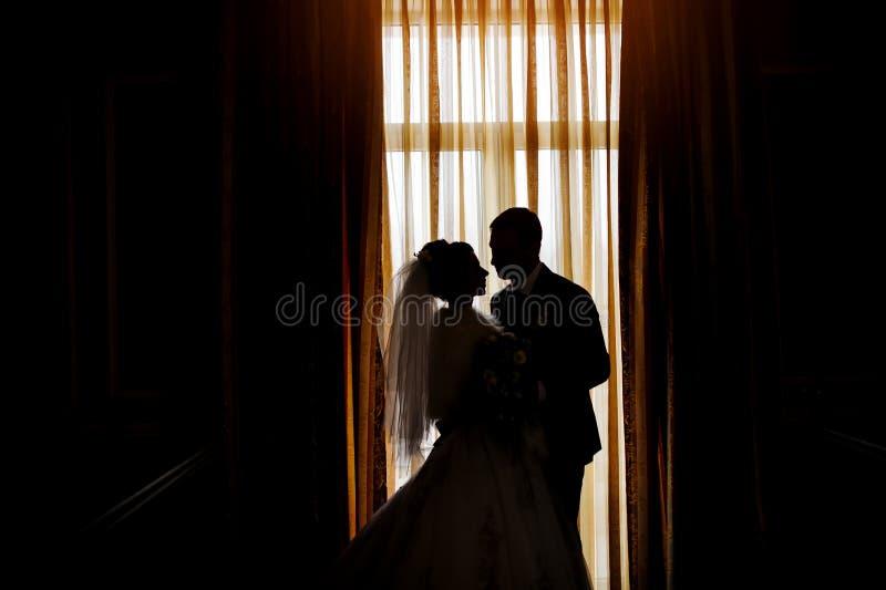 Siluetta di una sposa e di uno sposo sui precedenti dei wi di una finestra immagini stock