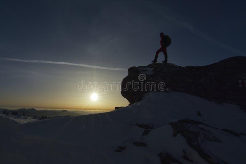 Siluetta di uno scalatore sul picco fotografie stock