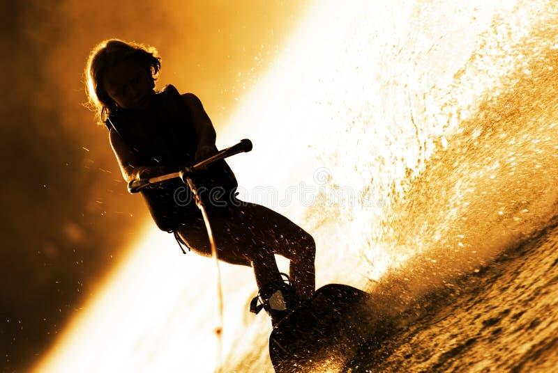 Siluetta di Wakeboarding della ragazza immagini stock libere da diritti