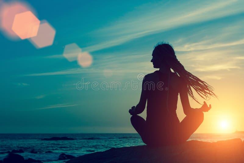 Siluetta di yoga della donna nella posizione di Lotus su una meditazione della spiaggia della roccia fotografia stock libera da diritti