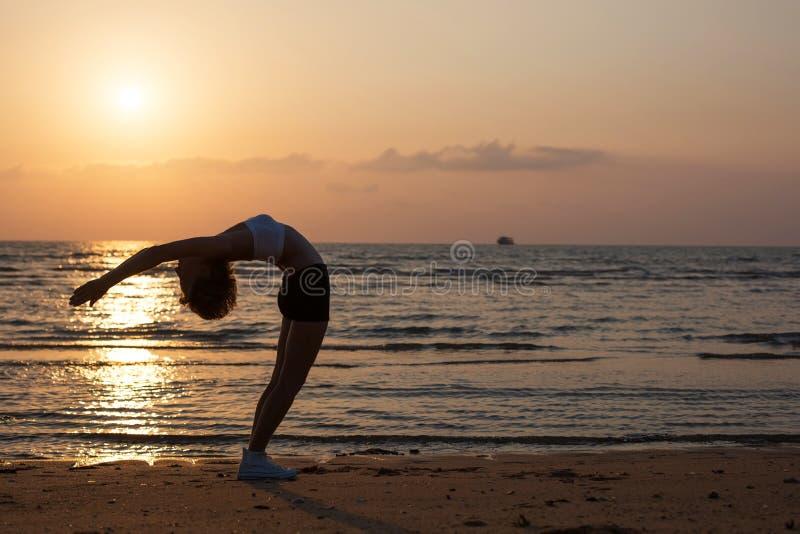 Siluetta di yoga sulla spiaggia fotografie stock libere da diritti