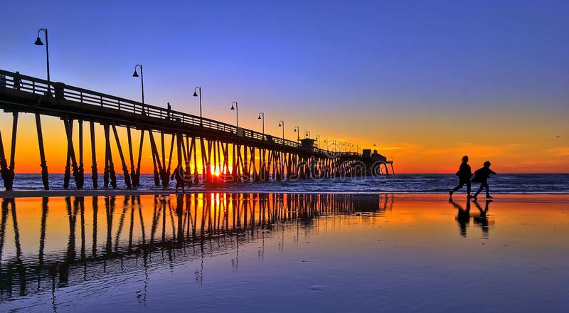 Siluetta e riflessioni della gente che cammina su una spiaggia fotografia stock