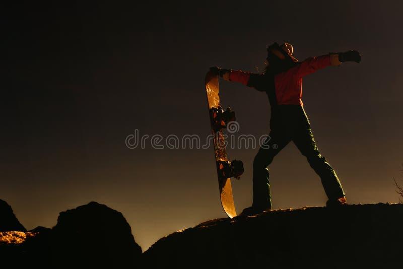 Siluetta femminile con lo snowboard al tramonto nelle montagne fotografie stock libere da diritti