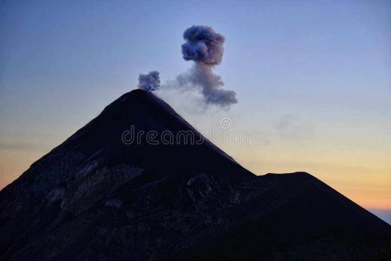 Siluetta Fuming di un'eruzione del vulcano attivo Fuego nel Guatemala fotografia stock libera da diritti