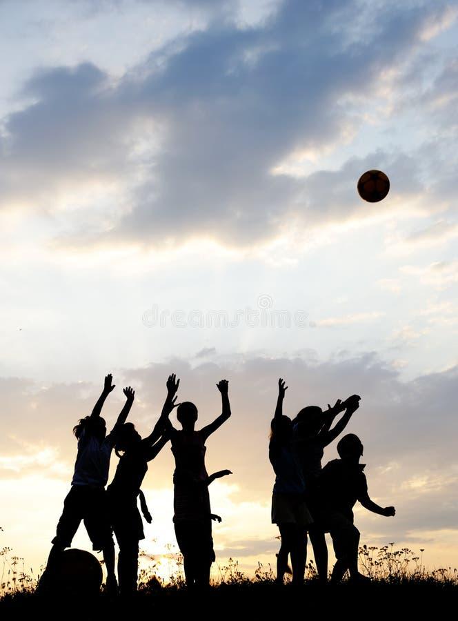 Siluetta, gruppo di bambini felici immagini stock libere da diritti