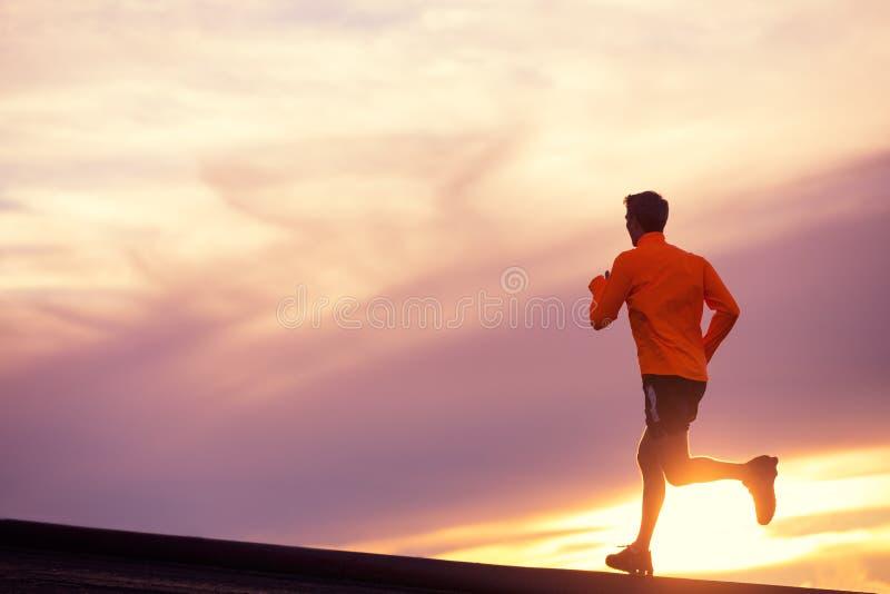 Siluetta maschio del corridore, imbattentesi in tramonto fotografia stock