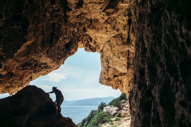 Siluetta maschio dello scalatore su una scogliera in una caverna fotografia stock