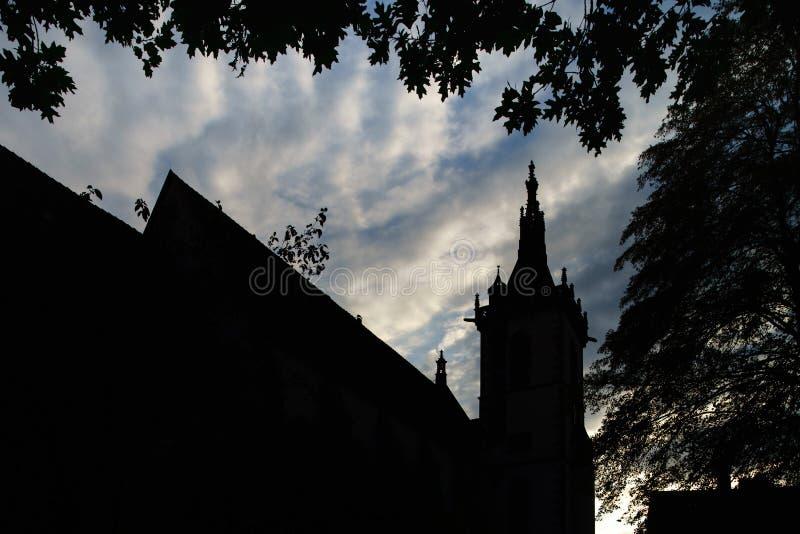 Siluetta nera della chiesa gotica medievale sul backgro del cielo di tramonto fotografia stock