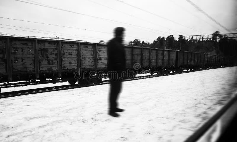 Siluetta sconosciuta della persona di un uomo mistico sconosciuto, stante sulla via, ai precedenti dei vagoni del treno merci fotografia stock