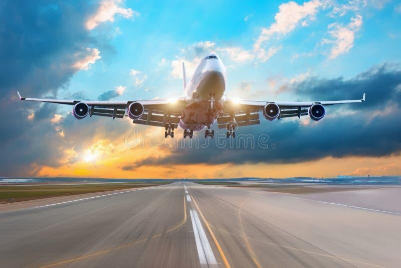 Siluetta scura dell'aeroplano enorme all'approccio di tramonto nell'aeroporto di bello bello cielo fotografie stock
