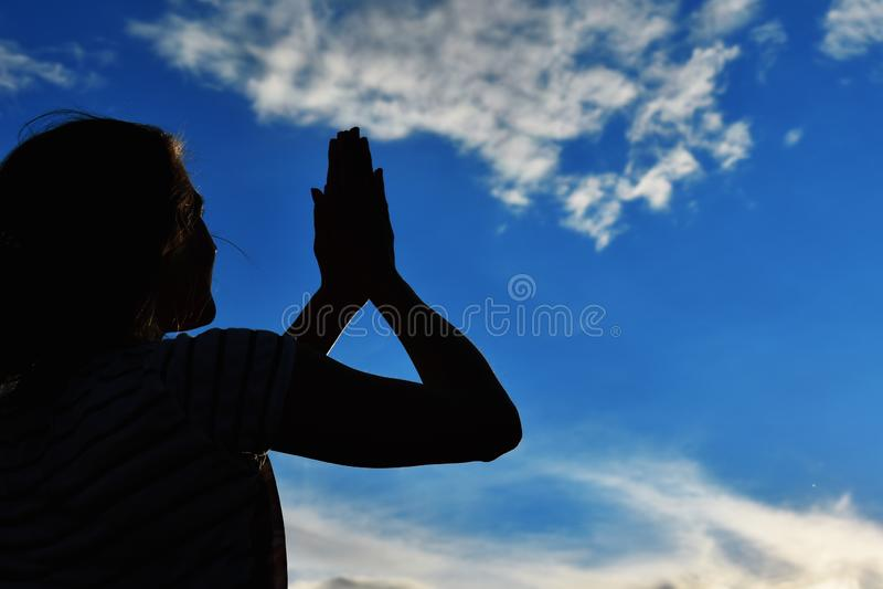 Siluetta scura delle mani femminili al tramonto in cielo Le palme si sono alzate al sole immagine stock