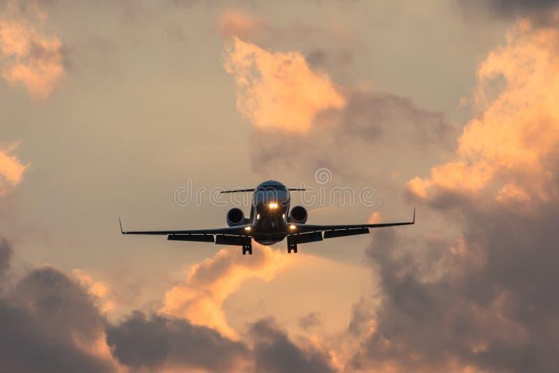 Siluetta scura di piccolo aeroplano all'approccio di tramonto nell'aeroporto di bello bello cielo immagini stock