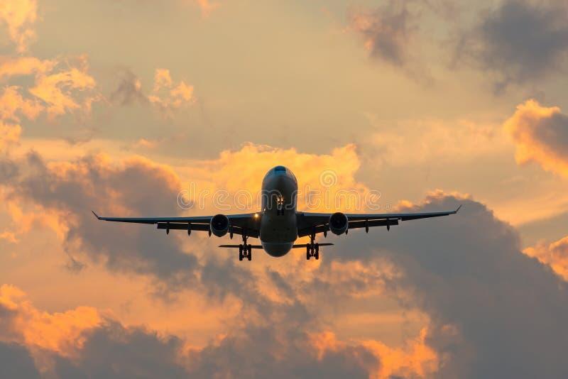 Siluetta scura di un aeroplano all'approccio di tramonto nell'aeroporto di bello bello cielo fotografia stock libera da diritti