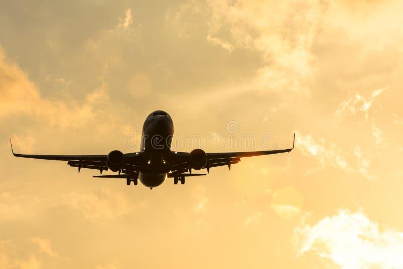 Siluetta scura di un aeroplano all'approccio di tramonto nell'aeroporto di bello bello cielo immagine stock libera da diritti