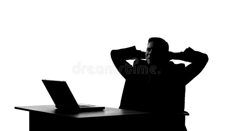 Siluetta smugly di seduta maschio sulla sedia dopo riuscito completamento dell'affare fotografie stock