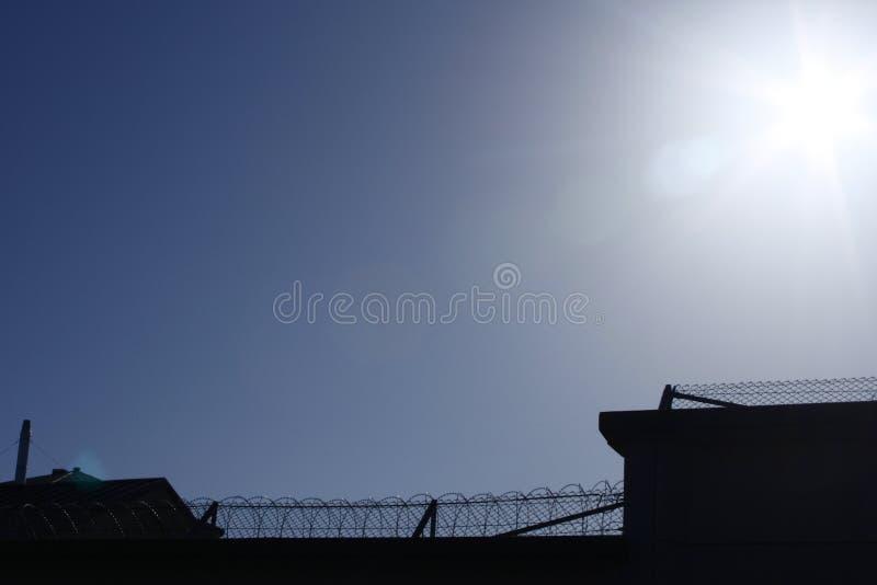 Siluetta sul recinto del filo spinato della prigione immagine stock libera da diritti