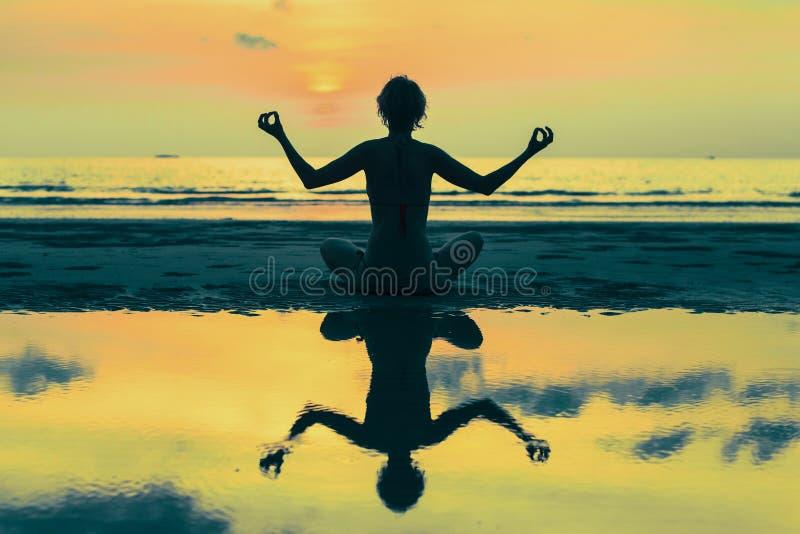Siluetta surreale di yoga della donna sulla spiaggia del mare distendasi fotografia stock libera da diritti